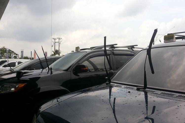 Deretan mobil yang parkir di area terbuka dengan posisi wiper diangkat.