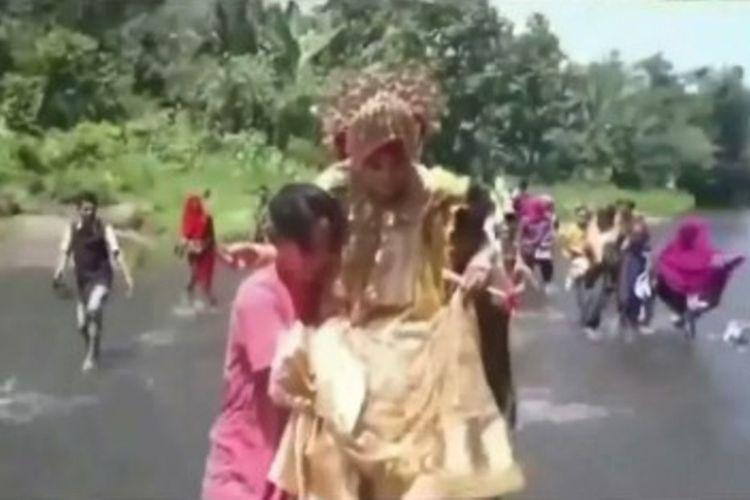Jumriah dari Desa Banteng harus ditandu melewati sungai untuk menuntaskan prosesi adat pernikahan Bugis Mapparola atau berkunjung balik ke rumah pengantin laki-laki, pada 2 Mei 2018 lalu. Pernikahan Jumriah dan Hasman ini akhirnya viral di media sosial. (KOMPAS.Com)