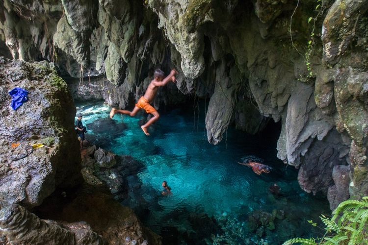 Anak-anak melompat ke kolam di Gua Hawang, Langgur, Maluku Tenggara, Kamis (15/3/2018). Gua ini merupakan salah satu tempat wisata di Maluku Tenggara(KOMPAS.com/RODERICK ADRIAN MOZES)