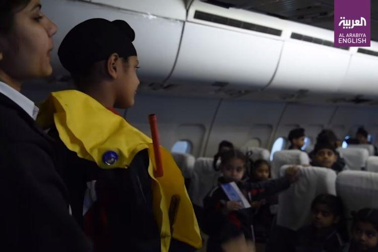 Anak-anak mendengarkan penjelasan penggunaan jaket pelampung, saat mengunjungi wahana simulasi penumpang pesawat di India.