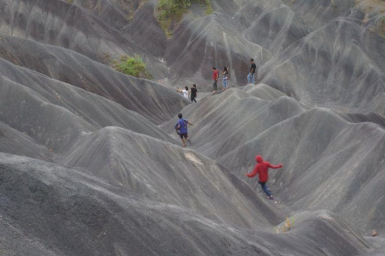 Pemandangan gumukan pasir dengan beberapa pengunjung yang sedang berlarian.