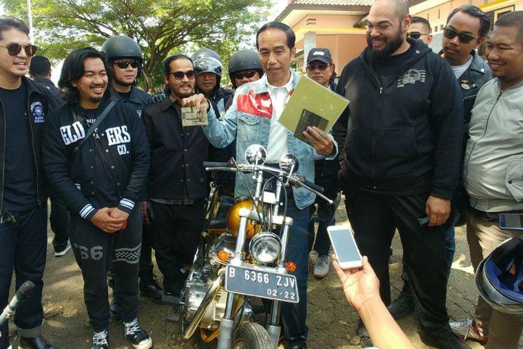 Presiden Joko Widodo memperlihatkan dokumen dan kelengkapan berkendara sebelum menjajal sepeda motor chopper miliknya di Sukabumi, Jawa Barat, Minggu (8/4/2018).