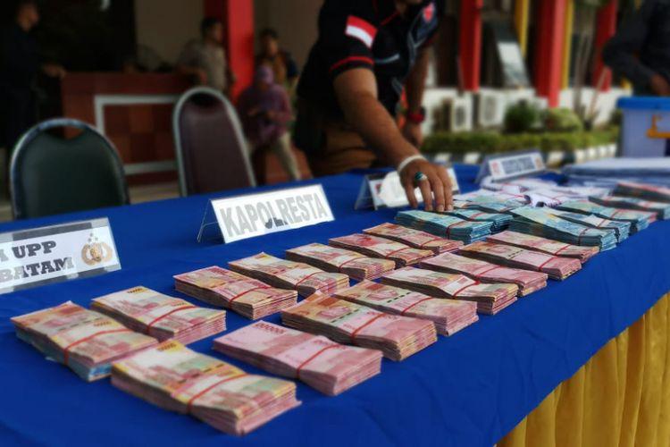 Salah seorang tim penyidik Saber Pungli Polresta Barelang sedang menyusun sejumlah uang yang merupakan barang bukti dari dugaan kasus pungli PPDB yang dilakukan di SMA Negeri 10 Sei Panas, Batam. Jumat (20/7/2018).