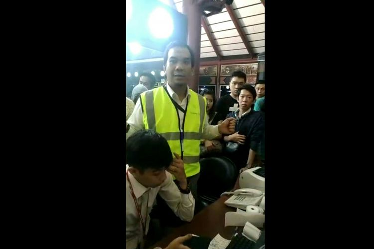 Salah satu petugas dari Sriwijaya Air saat dikerumuni calon penumpang di Bandara Internasional Soekarno Hatta meminta kejelasan terkait keberangkatan menuju Pontianak, Kamis (7/6/2018) malam.