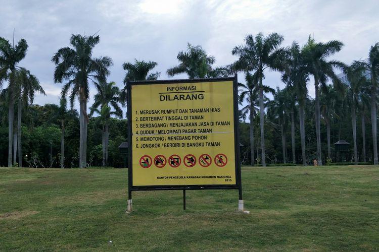 Pagar taman atau pagar pembatas rumput di kawasan Monas, Jakarta Pusat, telah dicopot. Namun, plang peringatan jangan merusak rumput masih terpasang. Foto diambil Kamis (11/1/2018).