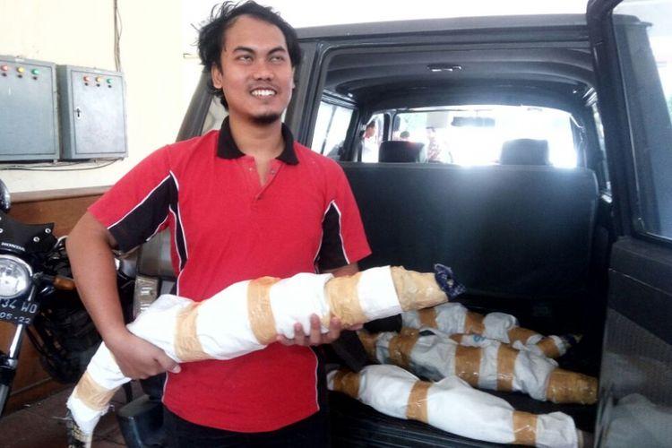Candra Gunawan saat menggendong salah satu buaya muara miliknya di Mapolda DIY.