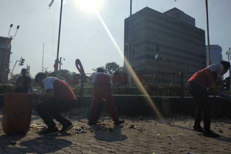 Petugas kebersihan di sekitar kawasan Sarinah membersihkan sampah batu yang digunakan para perusuh  di depan Bawaslu, Jakarta Pusat, Rabu (22/5/2019) malam.