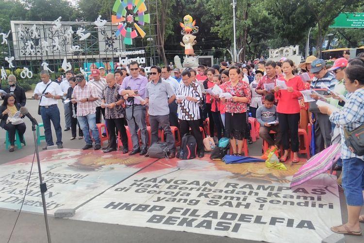 Sekitar 120 jemaat dari GKI Yasmin dan HKBP Filadelfia menggelar ibadah Minggu di seberang Istana Merdeka, Jakarta, pada Minggu (12/11/2017) karena dua gereja mereka masih disegel oleh pemerintah daerah setempat.