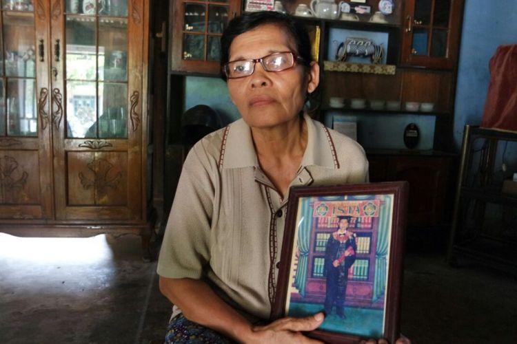 Sulastri, memegang foto wisuda anaknya, Dwi Hartanto yang lulus mengenyam pendidikan di Institut Sains dan Teknologi (IST) Akprind, Rabu ( 11/10/2017).