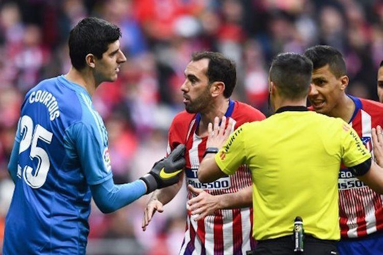 Thibaut Courtois tampak terlibat friksi dengan pemain lawan pada laga Atletico Madrid vs Real Madrid dalam lanjutan La Liga Spanyol di Stadion Wanda Metropolitano, 9 Februari 2019.