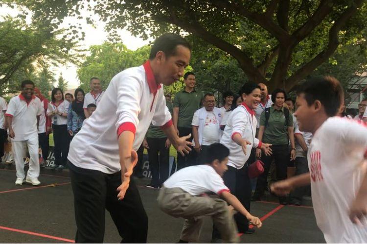 Presiden Joko Widodo dan Ibu Negara Iriana bermain permainan tradisional gobak sodor dengan anak-anak di halaman tengah Istana Presiden, Jakarta, Jumat (4/5/2018).