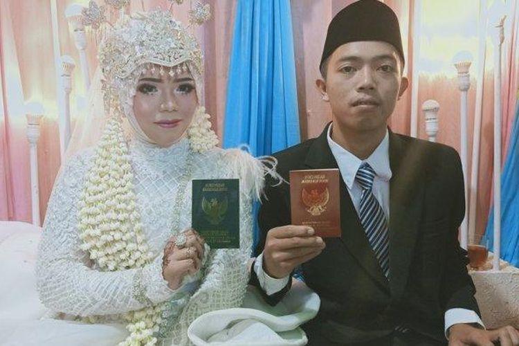 Muhammad Kusmantono (23) dan Niswatun Hasanah (19) melihatkan buku nikah usai menjalankan prosesi akad nikah. (Tribun Jateng)