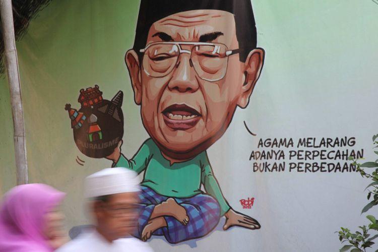 Warga melintas di depan spanduk yang mengutip pernyataan mantan Presiden RI KH Abdurrahman Wahid (Gus Dur) di kawasan Duren Sawit, Jakarta, Minggu (10/8/2014).