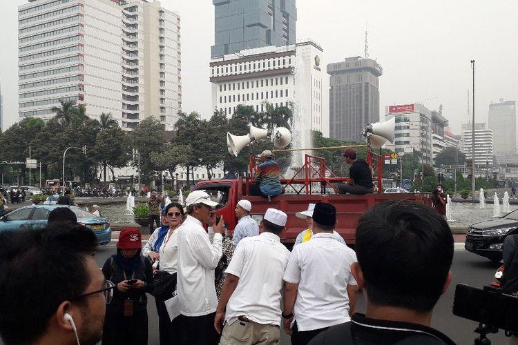 Mobil komando yang digunakan dalam aksi massa meninggalkan lokasi aksi di sekitar Patung Kuda, Jumat (14/6/2019) sore.