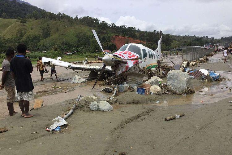 Sebuah pesawat rusak akibat terjangan banjir bandang di Sentani, Kabupaten Jayapura, Papua, Minggu (17/3/2019). Jumlah korban bencana banjir bandang yang terjadi pada Sabtu (16/3/2019) malam, hingga data yang masuk pada Minggu sore, terus bertambah menjadi 63 orang.