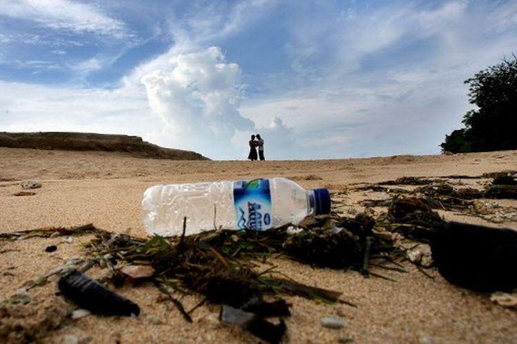 Dua wisatawan lokal mengunjungi di pantai dengan sampah rumput laut dan botol plastik di Nusa Dua, Bali, 4 Desember 2007.