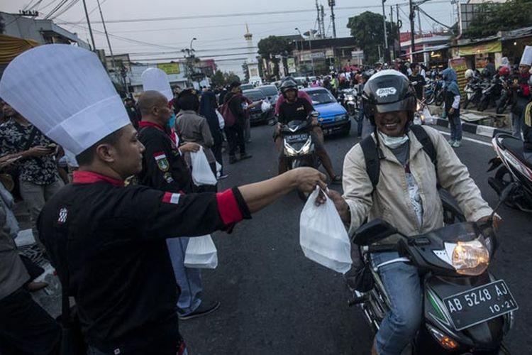 Petugas membagikan takjil kepada warga saat acara Cooking On The Road di Tugu Pal Putih, Yogyakarta, Minggu (3/6/2018). Acara yang digelar oleh Indonesia Chef Association (ICA) dan membagikan 5.678 takjil berupa nasi kebuli gratis kepada warga itu menjadi wujud berbagi kepada sesama saat bulan Ramadhan.