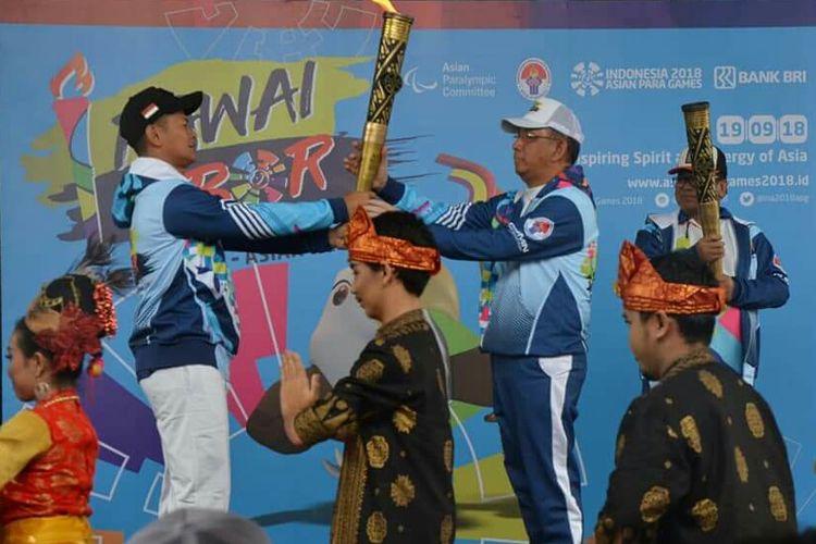 Ketua INAPGOC Raja Sapta Oktohari menyerahkan obor kepada Gubernur Kalbar, Sutarmidji saat pelepasan pawai obor Asian Para Games III di Pontianak (19/9/2018)