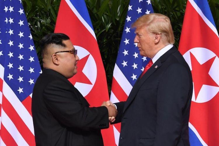 Pemimpin Korea Utara Kim Jong Un dan Presiden Amerika Serikat Donald Trump saling berjabat tangan untuk pertama kalinya di Hotel Capella, Singapura, Selasa (12/6/2018). (AFP/Saul Loeb)