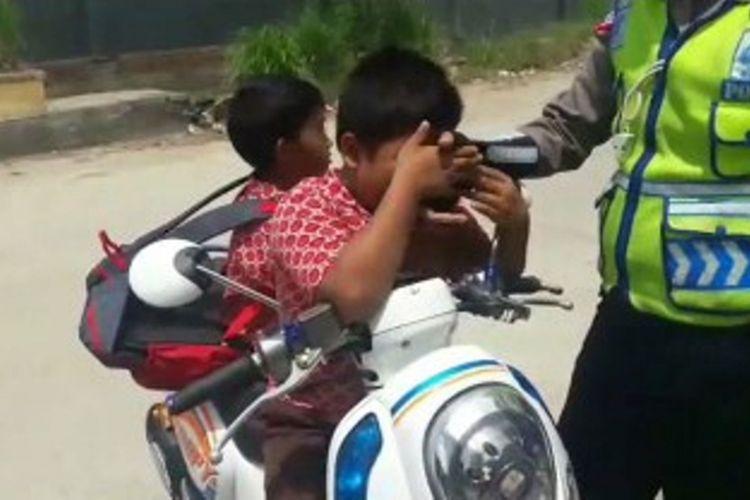 Dua bocah SD menangis sambil membujuk dan terus mencium tangan polisi agar ia dibebaskan dari tilang polisi.
