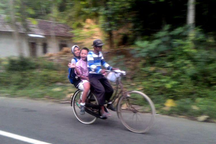 Hernowo mengendalikan kemudi sepeda, Kamilah dan Wahyu di belakang. Seperti inilah setiap hari Hernowo membawa Wahyu sekolah yang jauhnya belasan kilometer. Hernowo yang setengah tuli sejak lahir tidak menyerah menyekolahkan anaknya yang down syndrome. Di usia senja mereka, ia mengharapkan Wahyu bisa cepat mandiri.