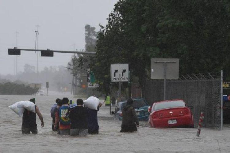 Warga mengevakuasi dirinya di Jalan Tol 90 di kota Houston setelah badai Harvey menimbulkan banjir dahsyat di kota terpadat di Texas tersebut.