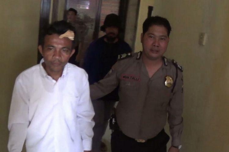 Faisal Pole (38) tengah melaporkan dirinya di Mapolsek Galesong, Kabupaten Takalar setelah menjadi korban pengeroyokan pelajar. Senin, (11/2/2019).