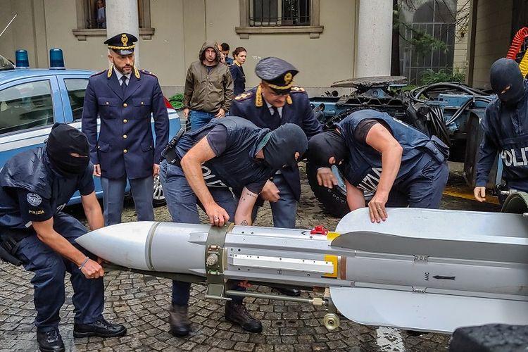 Foto yang dirilis kepolisian Italia, pada Senin (15/7/2019), menunjukkan petugas polisi yang membawa rudal Matra, sebagai bagian dari persenjataan yang disita dalam penggerebekan di Turin.