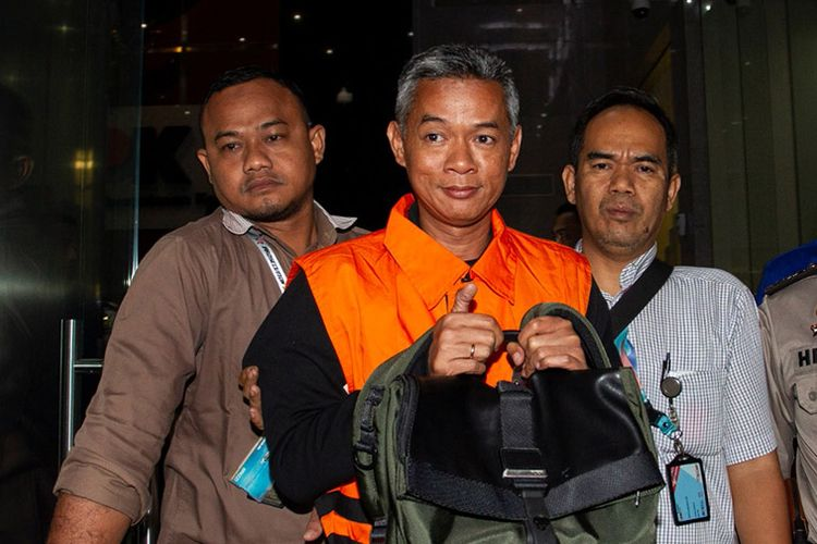 Komisioner KPU Wahyu Setiawan (tengah) mengenakan rompi tahanan usai menjalani pemeriksaan di gedung KPK, Jakarta, Jumat (10/1/2020) dini hari. KPK menetapkan empat orang tersangka dalam Operasi Tangkap Tangan (OTT) pada Rabu (8/1/2020) yakni WSE Komisioner KPU, ATF mantan anggota Bawaslu, serta HAR dan SAE dalam kasus dugaan penerimaan hadiah atau janji penetapan anggota DPR Terpilih 2019-2024 dengan barang bukti uang sekitar Rp 400 juta dalam bentuk mata uang dollar Singapura dan buku rekening.