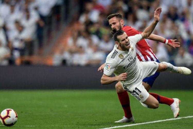 Pemain Real Madrid, Gareth Bale, terjatuh saat berduel dengan pilar Atletico Madrid, Saul Niguez, dalam pertemuan kedua tim pada laga pekan ke-7 Liga Spanyol di Santiago Bernabeu, Sabtu (29/9/2018).