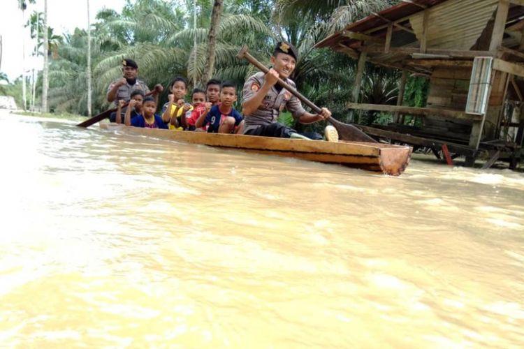 Polisi mengevakuasi korban banjir di Desa Lawang, Kecamatan Matangkuli, Kabupaten Aceh Utara, Kamis (18/10/2018).