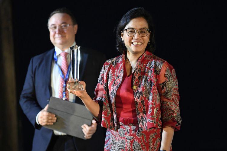 Menteri Keuangan Sri Mulyani Indrawati (kanan) menunjukkan piala pada sesi Global Market Award Ceremony dalam rangkaian Pertemuan Tahunan IMF - World Bank Group 2018 di Nusa Dua, Bali, Sabtu (13/10). Menteri Keuangan Sri Mulyani Indrawati mendapatkan penghargaan Finance Minister of the Year for East Asia Pacific Awards dari majalah ekonomi Global Markets. ANTARA FOTO/ICom/AM IMF-WBG/Anis Efizudin/wsj/2018.
