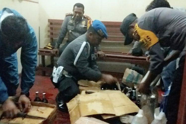 Polisi saat memeriksa barang bawaan penumpang kapal dan menemukan minuman keras (miras) jenis anggur merah yang dikemas dalam kardus di Pelabuhan Agats, Papua, Sabtu (22/9/2018).