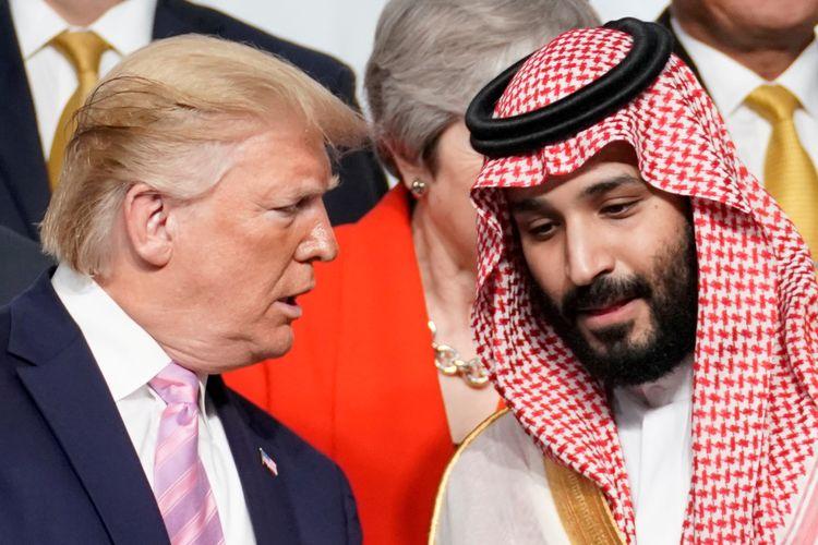 Presiden Amerika Serikat Donald Trump berbicara dengan Pangeran Mahkota Arab Saudi Mohammed bin Salman saat foto bersama dengan pemimpin lainnya dalam Konferensi Tingkat Tinggi G20 di Osaka, Jepang, Jumat (28/6/2019).