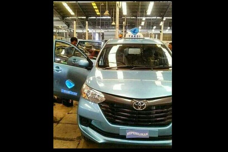 Gambar yang memperlihatkan sebuah mobil Toyota Transmover dengan warna dan logo khas Blue Bird tengah dirakit di sebuah pabrik.