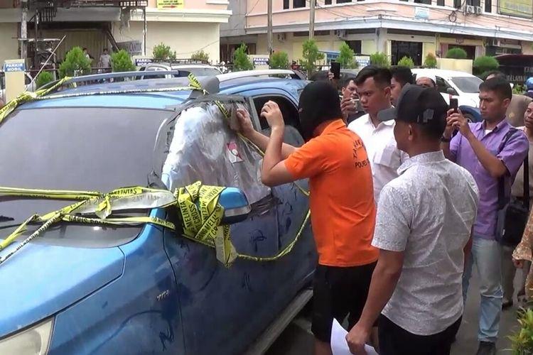 WJ (43) memperagakan saat tengah memecahkan kaca mobil korban menggunakan batu dalam reka ulang yang digelar penyidik Kepolisian Resor (Polres) Gowa, Sulawesi Selatan. Kamis, (11/4/2019).