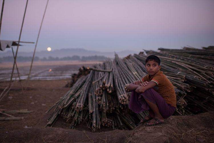 Anak pengungsi Rohingya duduk di dekat tumpukan bambu yang akan digunakan membangun tenda pengungsian di Naybara, Coxs Bazar.
