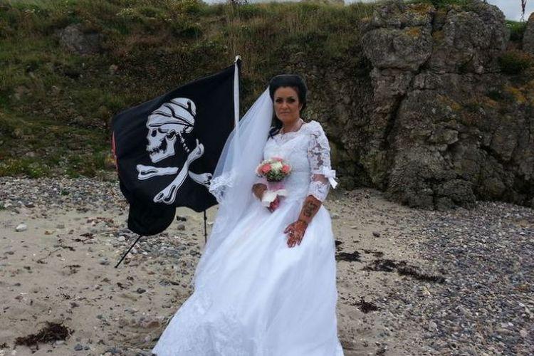 Amanda Teague (45) mengenakan gaun pengantin berdiri di samping bendera bajak laut usai melangsungkan pernikahan.