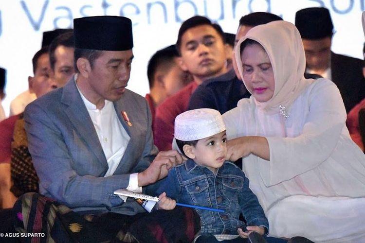 Presiden Jokowi sedang memakaikan jaket jins kepada cucunya, Jan Ethes saat merayakan Hari Santri Nasional di Solo, Minggu (21/10/2018).
