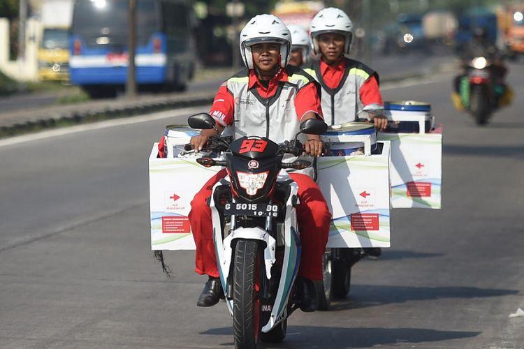 Petugas bermotor pengantar BBM dari KiosK Pertamax SPBU Muri berkeliling jalur pantura di Tegal, Jawa Tengah, Rabu (30/5). Pertamina menyiagakan 60 titik Kios BBM Kemasan atau KiosK Pertamax sebagai salah satu alternatif bagi pemudik untuk mendapatkan BBM selain di SPBU. ANTARA FOTO/Akbar Nugroho Gumay/aww/18.