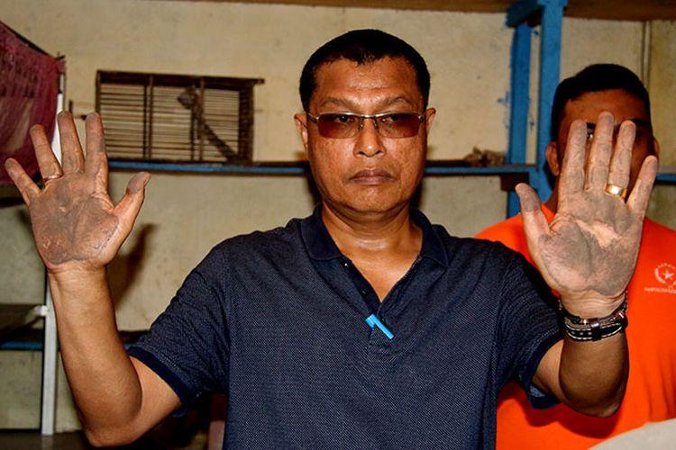Mahdinur, kapala Bidang Mineral dan Batubara pada Dinas ESDM Aceh memperlihatkan telapak tangannya terkena debu batu bara di rumah warga Desa Peunga Cut Ujong, Kecamatan meureubo Aceh Barat dan Desa Suak Puntong Nagan Raya, Sabtu (19/08/17).