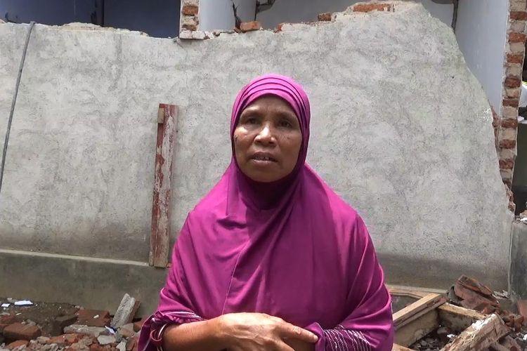 Ibu Rumida di belakang rumahnya yang terdampak gempa, Kamis (21/3/2019).