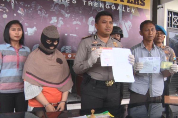 Pelaku (kepala ditutup) penipuan berkedok perjalanan ibadah umrah ditangkap jajaran Polres Trenggalek, Jawa Timur, Rabu (18/4/2018).