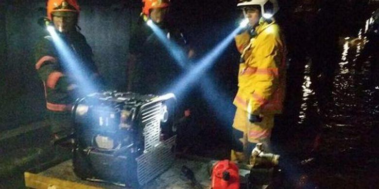 Petugas gabungan berusaha mengeringkan genangan air di terowongan bawah tanah antara Stasiun Bishan dan Braddell, Sabtu (7/10/2017)