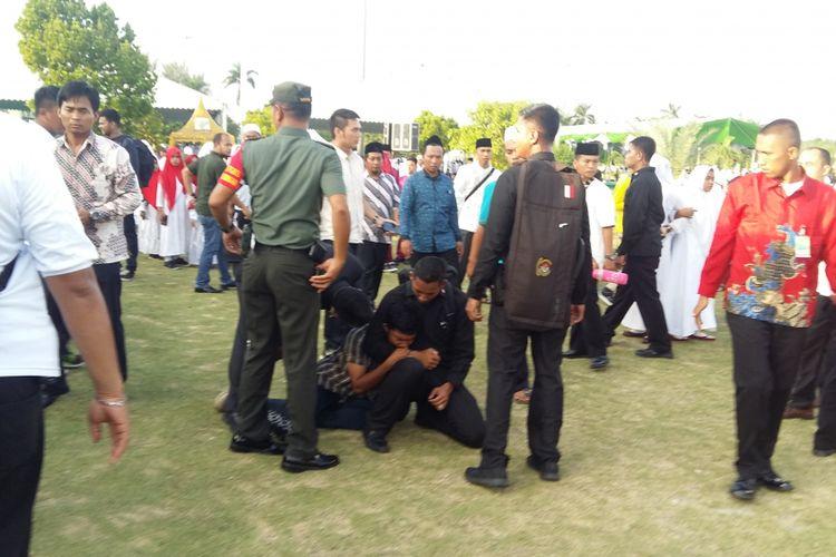 Seorang pemuda diamankan petugas karena dianggap mengacau saat Presiden Joko Widodo (Jokowi) akan meninggalkan tempat acara pada Harlah NU ke-92 di depan halaman masjid An Nur, Pekanbaru, Riau, Rabu (9/5/2018). (Kontributor Kompas TV Pekanbaru, Citra Indriani)