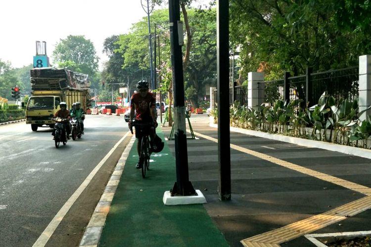 Seorang pesepeda bernama Yupa bersepeda di jalur sepeda trotoar Jalan Asia Afrika, Senayan, Jakarta, Selasa (31/7/2018). Jalur khusus sepeda itu terhalang tiang.