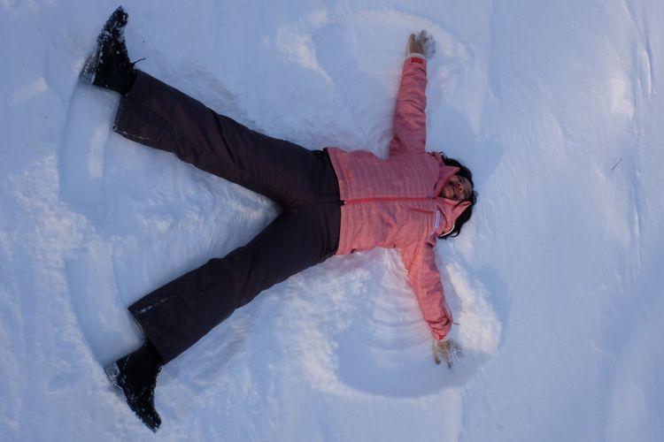 Membuat snow angel di atas salju tebal.