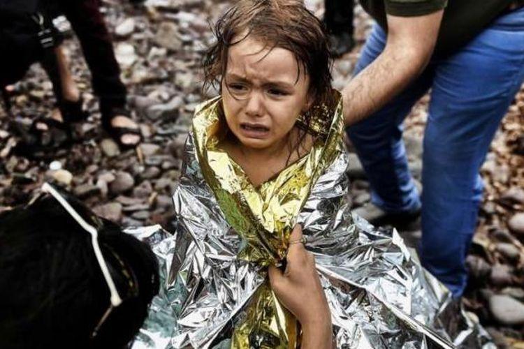 Seorang anak perempuan pengungsi Suriah menangis saat tiba di Pulau Lesbos, Yunani, setelah menyeberangi laut Aegean dari Turki, 28 September 2015.