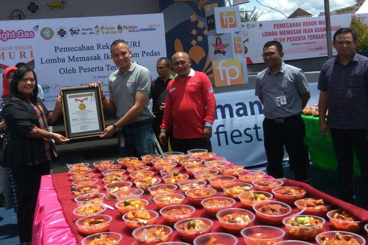 Manager Muri, Sri Widayati menyerahkan piagam Rekor Muri Memasak Ikan Asam Pedas dengan Peserta Terbanyak kepada Marketing Branch Manager Pertamina Kalbarteng Teuku Johan Miftah, di Pontianak,  Kalimantan Barat, Minggu (25/2/2018).