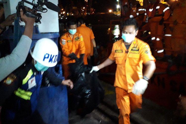 Petugas Basarnas menurunkan kantong jenazah dari KN SAR Sadewa di Dermaga JICT 2 Pelabuhan Tanjung Priok, Kamis (8/11/2018).